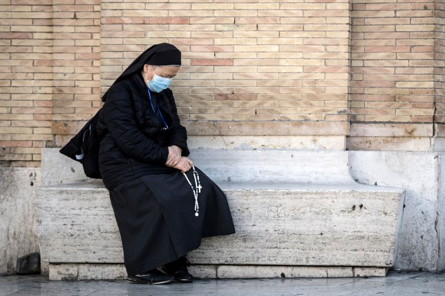 A nun prays during Angelus Prayer in St. Peter Square in Vatican, in Rome, Italy