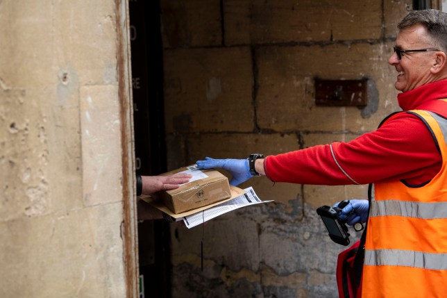17.03.20. Coronavirus Pandemic, Bath, Somerset. A Royal Mail postman makes deliveries wearing rubber gloves in Bath, Somerset, after the UK government announced stricter measures and social distancing advice to deal with the coronavirus outbreak. PIC ? Andrew Lloyd