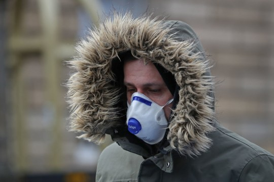 A man wears a face mask on the Royal Mile in Edinburgh. PA Photo. Picture date: Wednesday March 18, 2020. See PA story HEALTH Coronavirus. Photo credit should read: Andrew Milligan/PA Wire