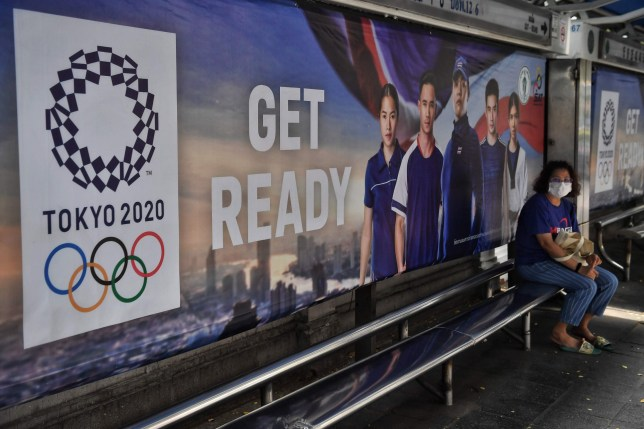 A woman wears a face mask amid concerns over the spread of the COVID-19 coronavirus as she sits at a bus stop advertising the Tokyo 2020 Summer Olympics in Bangkok on March 20, 2020. (Photo by Lillian SUWANRUMPHA / AFP) (Photo by LILLIAN SUWANRUMPHA/AFP via Getty Images)