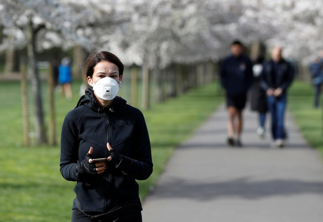 A woman wearing a protective face mask walks by blossom trees in Battersea Park