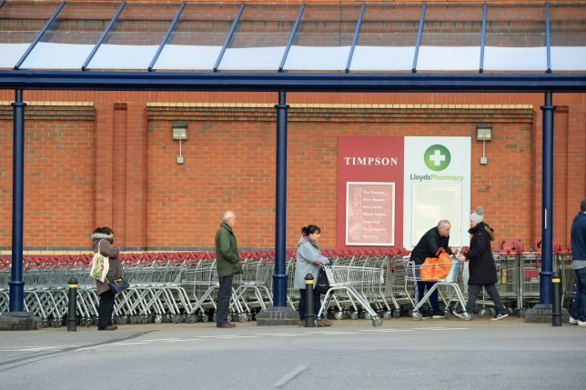 People observe social distance while queuing in a Sainsbury supermarket