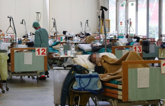 epa08319281 Health workers at work in the temporary structures built next to the Brescia hospital due to the coronavirus outbreak, Brescia, Italy, 24 March 2020. Tighter lockdown measures come into force as Italy remains under lockdown. Countries around the world are taking increased measures to stem the widespread of the SARS-CoV-2 coronavirus which causes the Covid-19 disease. EPA/FILIPPO VENEZIA Patient's face pixelated due Italian privacy laws