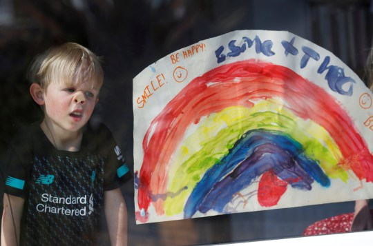 a young boy looks out of the window next to his rainbow painting