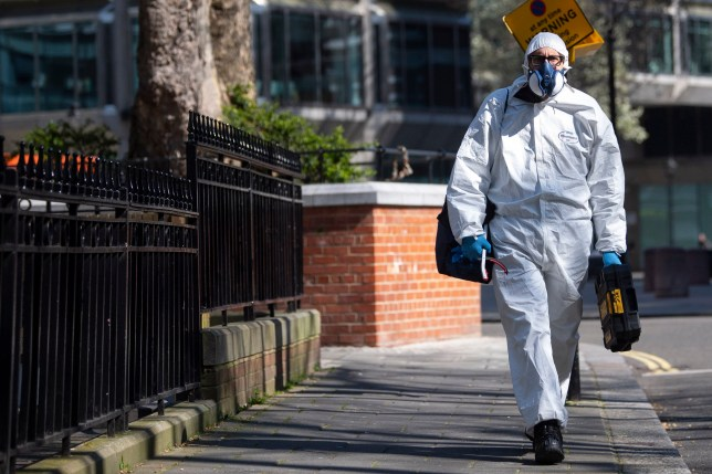 A man wearing a protective face mask and clothing in Westminster, London after Prime Minister Boris Johnson put the UK in lockdown to help curb the spread of the coronavirus. PA Photo. Picture date: Thursday March 26, 2020. The UK's coronavirus death toll reached 463 on Wednesday. See PA story HEALTH Coronavirus. Photo credit should read: Victoria Jones/PA Wire