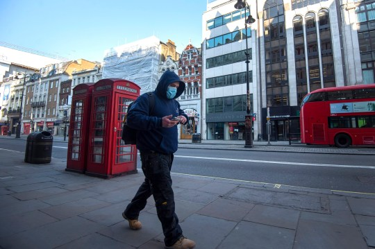 A man wearing a protective face mask during rush hour on the Strand in Westminster, London after Prime Minister Boris Johnson put the UK in lockdown to help curb the spread of the coronavirus.