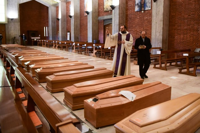 Priest Don Marcello gives a blessing to the coffins of deceased people inside the church of San Giuseppe in Seriate, on March 28, 2020. (Photo by Piero CRUCIATTI / AFP) (Photo by PIERO CRUCIATTI/AFP via Getty Images)