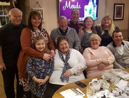 Susan Nelson middle with her family. See SWNS story SWMDfamily; The children of a beloved mum, who died after contracting Coronavirus, believe that up to 17 wider family members have been infected Covid-19 after they all attended a funeral. Susan Nelson, 65, who had no underlying health conditions, died at the Queen Elizabeth Hospital in Birmingham with her husband Robert, 67, at her side.The retired grandmother, who ran a family catering business and a sandwich shop in her native Halesowen, West Mids., displayed symptoms after her aunt?s funeral on Friday March 13. Her condition got notably worse the following week, with the family forced into calling an ambulance. Her son Carl, 42, who now lives in Cleckheaton, Yorks., said: ?She was coughing a lot, very breathless and showing all the traditional symptoms. ?She was admitted to hospital on Monday (16/03) and I spoke to the hospital staff the following day. ?They said the next 48 hours were critical before they called me back a few hours later to say it was very close to the end and one member of the family could be with her.