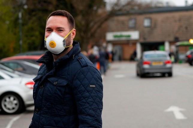 A man wears a protective face mask outside a Waitrose supermarket