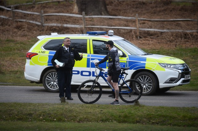 A police patrol stops to speak to a cyclist in Richmond Park, in Richmond upon Thames, southwest London, as the UK continues in lockdown