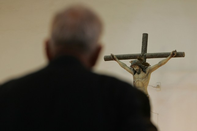 A man prays in front of a cross