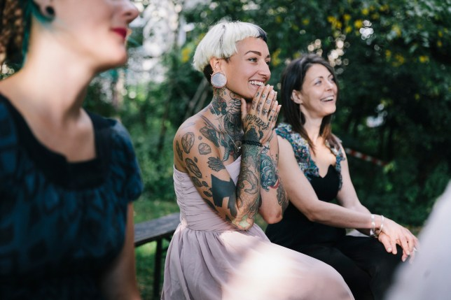 Tattooed wedding guest clasping her hands together as lesbian couple gets married.