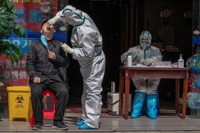 epa08336376 A medical worker wearing a full protective outfit tests a man for Covid-19 symptoms in a street in Wuhan, China, 01 April 2020. Wuhan, the epicenter of the coronavirus outbreak, partly lifted the lockdown allowing people to enter the city after more than two months. According to Chinese government figures over 2,500 people have died of Covid-19 in Wuhan since the outbreak began. EPA/ROMAN PILIPEY