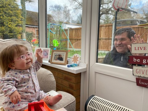 Mum shares powerful photo of toddler with rare genetic condition waving to her dad through a window to urge people to stay home