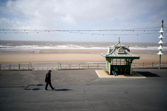 A lone police officer patrols the promenade on Blackpool's Golden Mile.