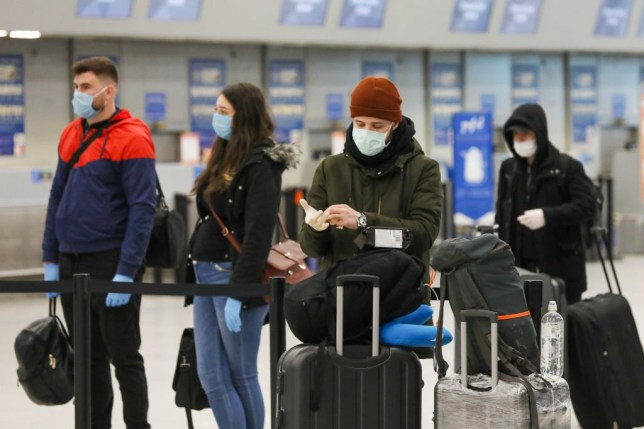 Passengers wearing face masks prepare to check-in at London Luton Airport in Luton, U.K., on Monday, March 30, 2020. EasyJet Plc grounded its entire fleet after completing customer-repatriation flights, and said it's in talks to build a cash cushion to see it through the gap in business caused by the coronavirus. Photographer: Chris Ratcliffe/Bloomberg via Getty Images