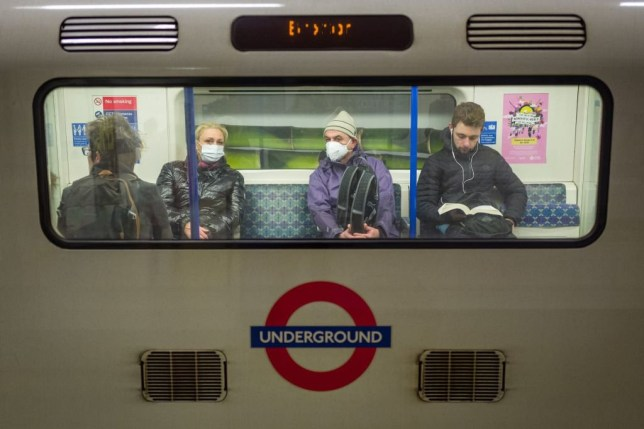 Passengers wear protective face masks as they travel on an underground train on the Victoria Line in London on March 15, 2020. (Photo by Tolga AKMEN / AFP) (Photo by TOLGA AKMEN/AFP via Getty Images)
