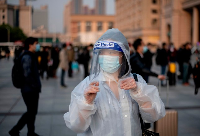 A person wearing a face mask arrives at Hankou Railway Station