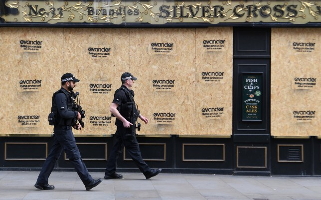 epa08350805 Armed police walk past a boarded up pub in London, Britain, 08 April 2020. According to news reports, new ways of boarding London's buses are being looked at to reduce contact for drivers during the coronavirus pandemic. Nine bus workers have now died in the UK from Covid-19, Transport for London (TfL) is calling for passengers to board buses using the middle door to reduce passengers' contact with drivers. EPA/ANDY RAIN