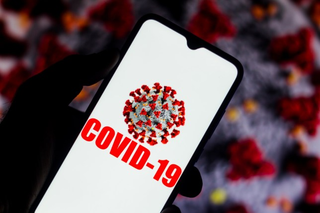 In this photo illustration the Covid-19 virus is displayed on the smartphone screen. Coronavirus appears in the background