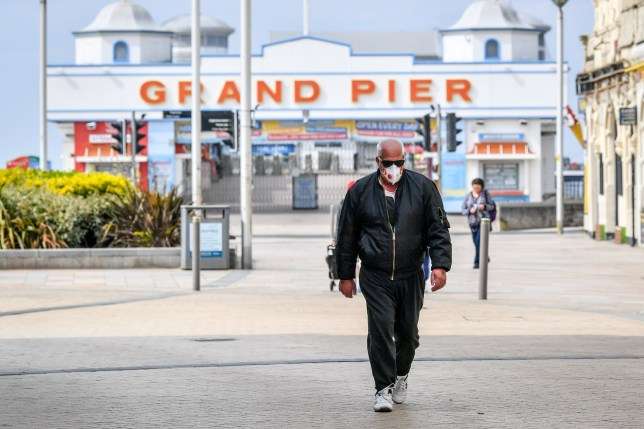 A man wearing a mask walks in front of the closed Grand Pier around midday on Easter Sunday at Weston-super-Mare as the UK continues in lockdown to help curb the spread of the coronavirus.