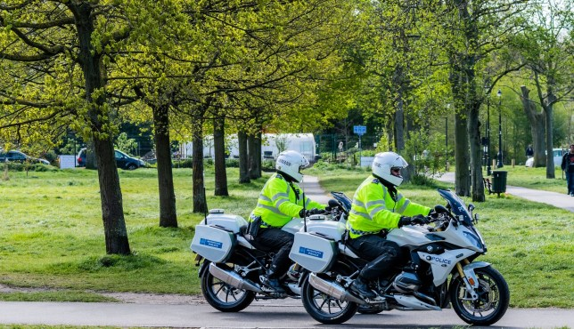 Two police motorbikes make a sweep of the common to check enforcement of the guidance of lockdown