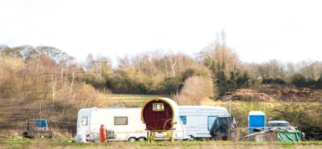A typical gypsy camp site set up in a random field at the side of a motorway.