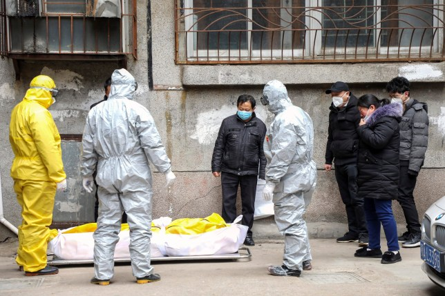 FILE - In this Feb. 1, 2020, file photo, funeral home workers remove the body of a person suspected to have died from the coronavirus outbreak from a residential building in Wuhan in central China's Hubei Province. The central Chinese city of Wuhan has raised its number of COVID-19 fatalities by more than 1,000. State media said the undercount had been due to the insufficient admission capabilities at overwhelmed medical facilities at the peak of the outbreak. (Chinatopix via AP, File)