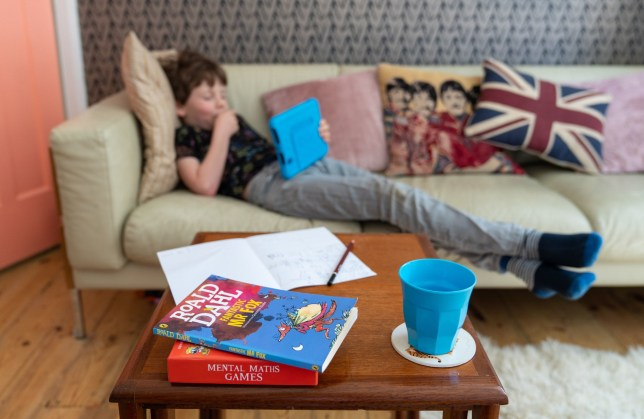 Wilfred, aged 7, reads on a kindle tablet as he takes part in home schooling at home in London, as schools reopen after the Easter break but classroom attendance is limited to the children of key workers while the UK continues in lockdown to counter the spead of coronavirus. PA Photo. Picture date: Monday April 20, 2020. Education Secretary Gavin Williamson said Sunday that no date has been set for re-opening schools in England. See PA story HEALTH Coronavirus Education. Photo credit should read: Dominic Lipinski/PA Wire
