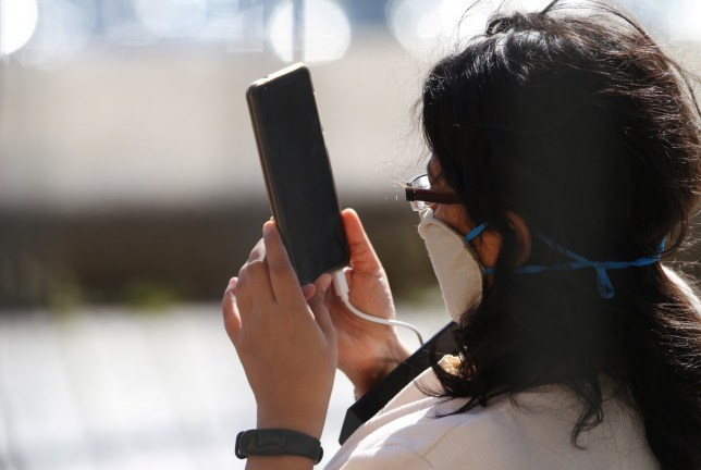 A woman wearing a protective face mask holds a mobile phone