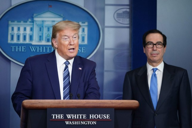 US President Donald Trump speaks as Treasury Secretary Steven Mnuchin listens during the daily briefing on the novel coronavirus, COVID-19, in the Brady Briefing Room of the White House in Washington, DC on April 21, 2020. (Photo by MANDEL NGAN / AFP) (Photo by MANDEL NGAN/AFP via Getty Images)