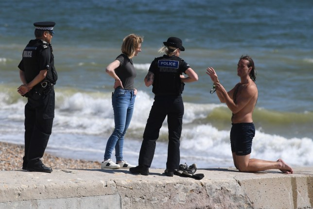 Police officers try to persuade a sunbather to leave the beach in Brighton