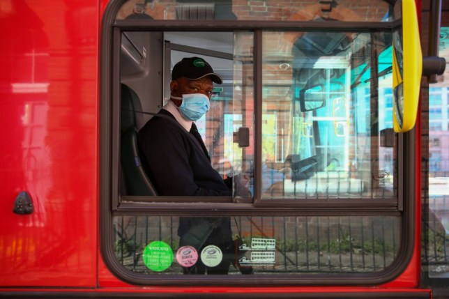 A bus driver wearing a protective face mask and gloves poses for a photograph in London, U.K., on Wednesday, April 22, 2020. Boris Johnson's coronavirus strategy faces its first major political test since the U.K. was put on lockdown a month ago when members of Parliament question ministers in a sitting conducted via video-conference. Photographer: Hollie Adams/Bloomberg via Getty Images