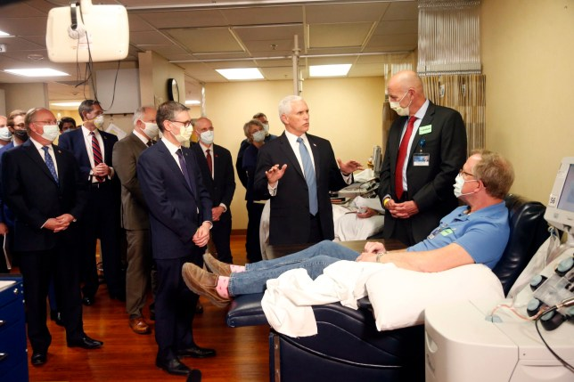 Vice President Mike Pence, center, and Dr. Michael Joiner visit with Dennis Nelson, right, who survived the coronavirus, during Pence's visit to the Mayo Clinic Tuesday, April 28, 2020, in Rochester, Minn., where he toured the facilities supporting COVID-19 research and treatment. (AP Photo/Jim Mone)