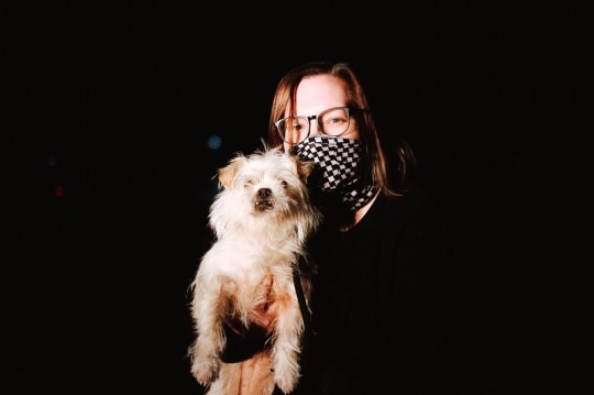A woman wearing a face mask and holding a dog against a black background