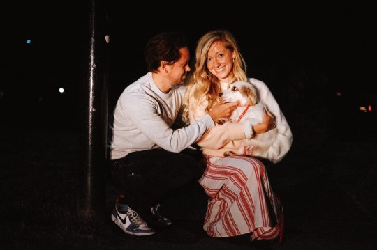 A woman and a man holding a dog wrapped in a blanket