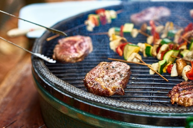 Succulent steak cooking on bbq grill with vegetables