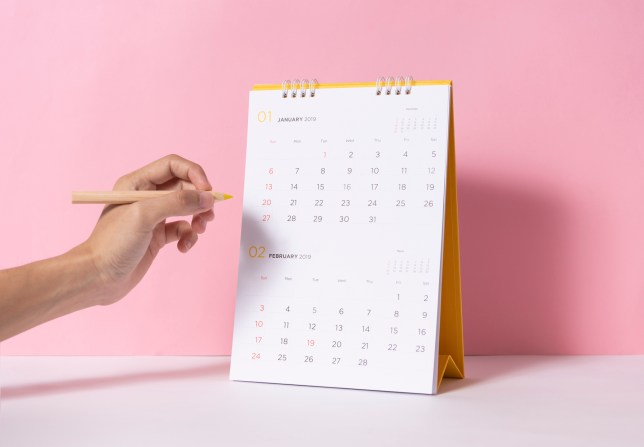 Cropped Hand Of Person Holding Colored Pencil By Calendar On Table.