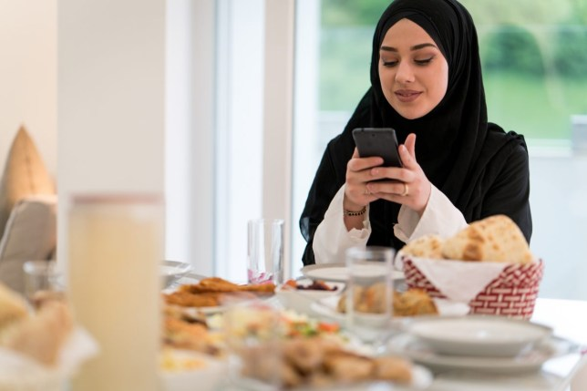 Muslim girl with hijab taking photo of lunch table