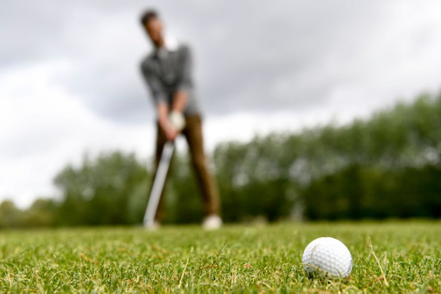 Person playing golf outdoors