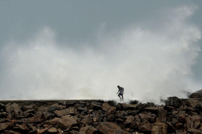 man walking next to wave
