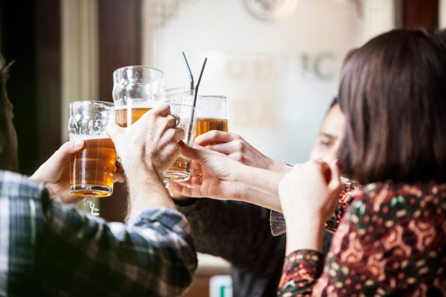 A group of friends in a pub toasting with pint glasses