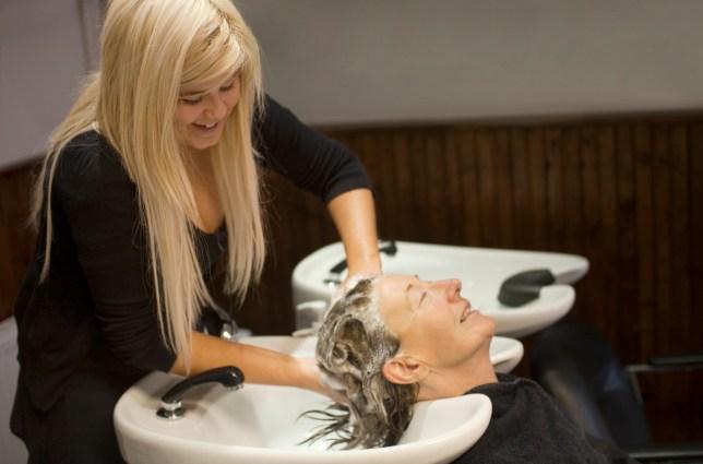 Hairdresser washing customer's hair in beauty salo