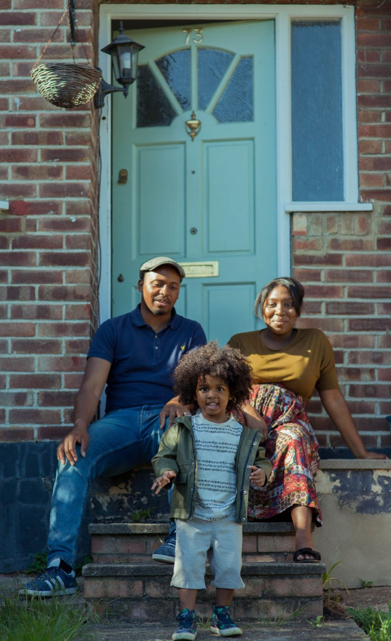 Fran Nelson portrait at the door: Tasha, Jason and their three-year-old son