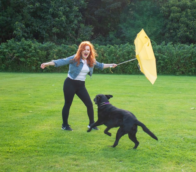 Lucy and Olga outside on grass. Lucy is holding a yellow umbrella, which is inside out.
