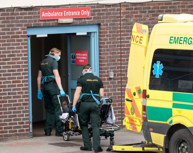 Ambulance crew wear protective equipment while moving a patient from a vehicle at Doncaster Royal Infirmary