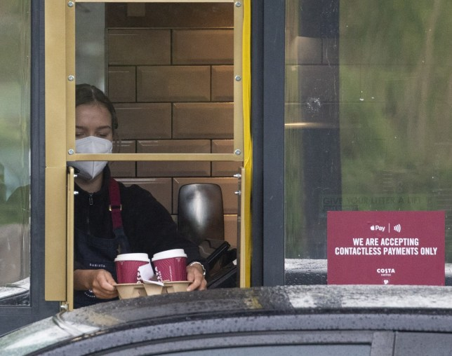 Staff member with face mask as drivers queue for coffee at Costa Drive Thru, Cameron Toll, Edinburgh. May 4 2020 Costa is one of the businesses to have re-opened to serve takeaway customers after a period of being closed.