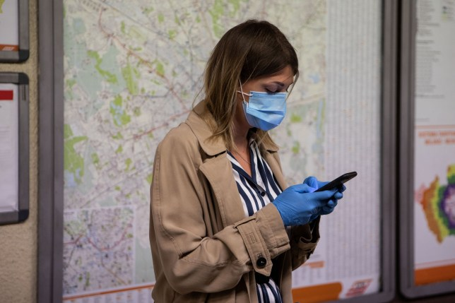 A woman wearing protective mask and gloves uses a mobile phone while waiting for a train at M1 underground line Cadorna station in Milan, Italy. (Photo by Emanuele Cremaschi/Getty Images)