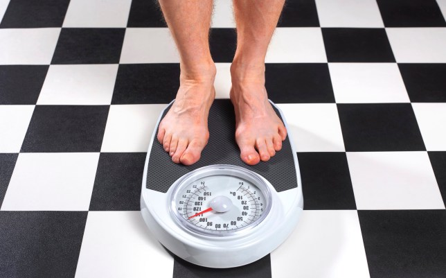 Senior obese man measuring his weight on bathroom scales
