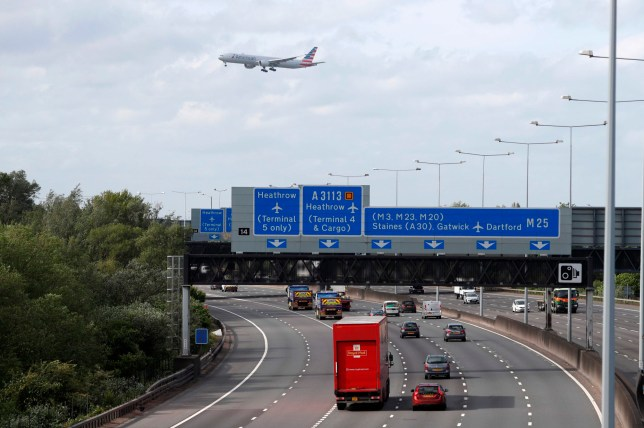 Traffic is seen on the M25 motorway as a plane flies overhead during the morning rush hour near Heathrow Airport in west of London on May 11, 2020. - British Prime Minister Boris Johnson on May 10 announced a phased plan to ease a nationwide coronavirus lockdown, with schools and shops to begin opening from June 1 -- as long as infection rates stay low. (Photo by Adrian DENNIS / AFP) (Photo by ADRIAN DENNIS/AFP via Getty Images)